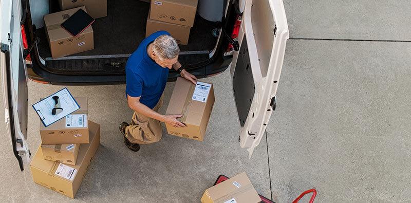 Kurier niosący paczkę zpaki dostawczaka